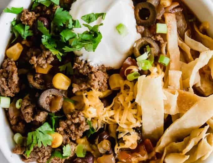 Bowl filled with Easy Taco Soup topped with sour cream, cilantro, tortilla strips and melty cheese.