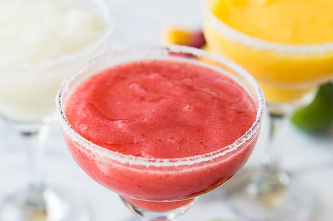Ever wonder how to make restaurant style margaritas at home?! These fruity, slushy margaritas are made using real fruit and are an absolutely perfect cocktail for sipping on!