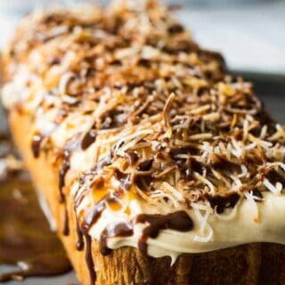 An easy to make dessert! Pound cake topped with a fluffy caramel buttercream frosting, toasted coconut, and a decadent drizzle of caramel and chocolate on top.