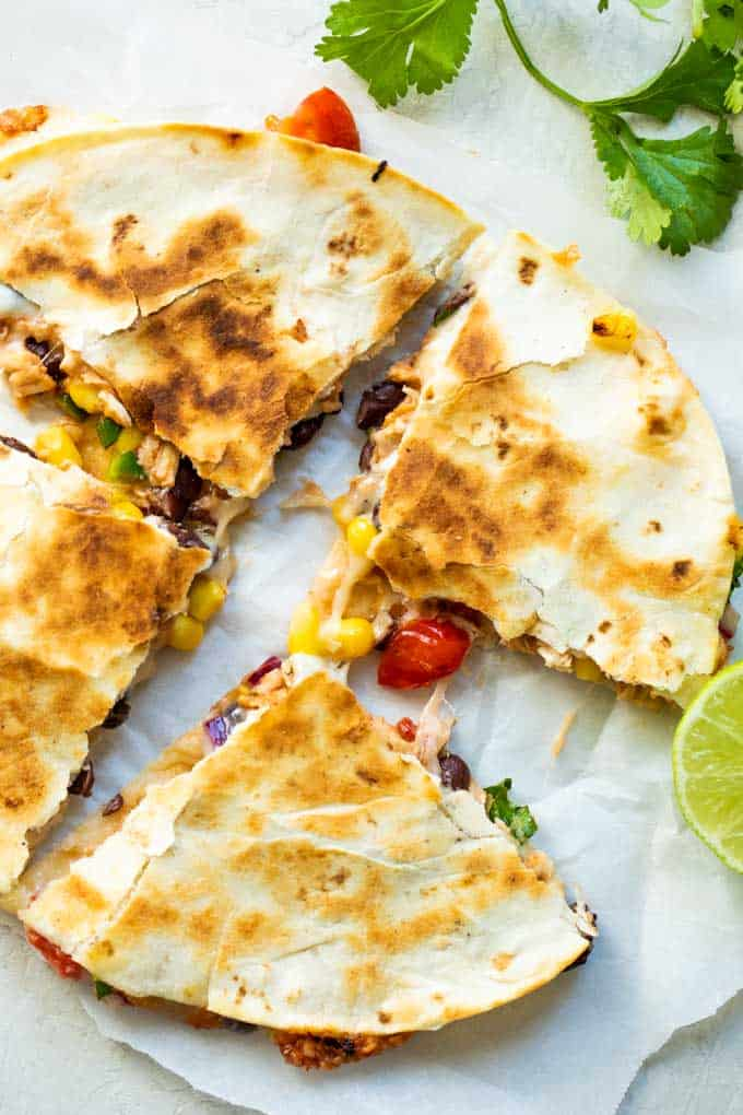 Cowboy Quesadilla on a piece of parchment paper, cut into 4ths with melty cheese strung between the slices.