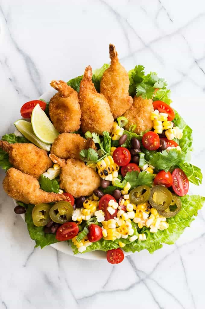 Shrimp Taco Salad with the perfect Southwestern Dressing! This salad is perfect for summertime, bursting with flavor and a little spice.