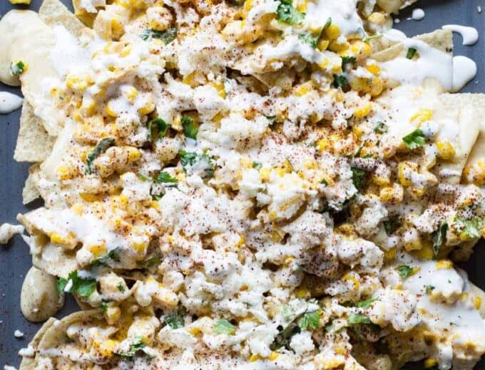 Mexican Street Corn Nachos! Chips loaded up with all the flavors of a classic mexican street corn and smothered with a creamy, spicy queso blanco.