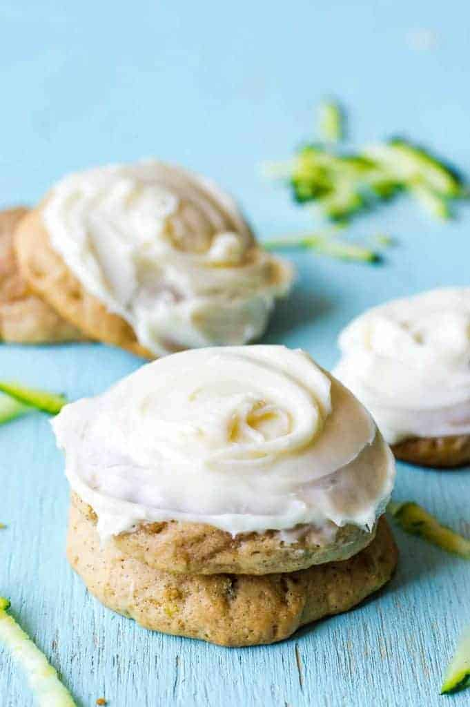 Stacked Zucchini Cookies with a swirl of cream cheese frosting.