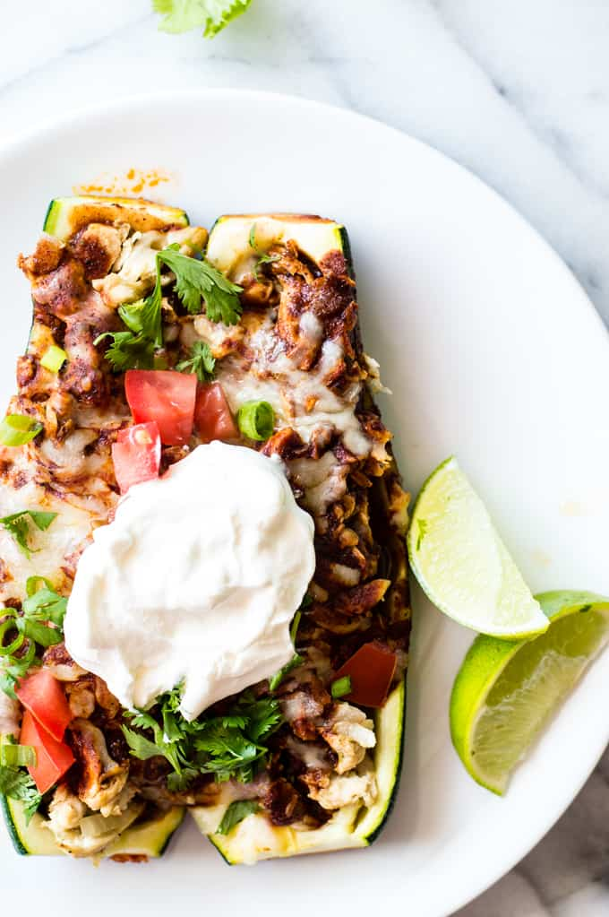Two chicken enchilada zucchini boats on a plate topped with sour cream.