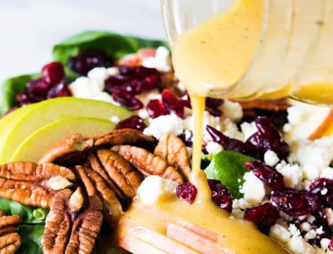 Autumn Apple Salad in a large salad bowl being drizzled with Maple Dijon Vinaigrette.