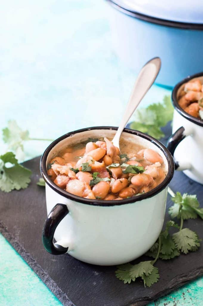 Charro Beans, or Cowboy Beans, are a classic Tex Mex side dish of pinto beans flavored with garlic, onion, and spiced up with some chiles. This version is made easy with the slow cooker! The perfect complement to any meal!