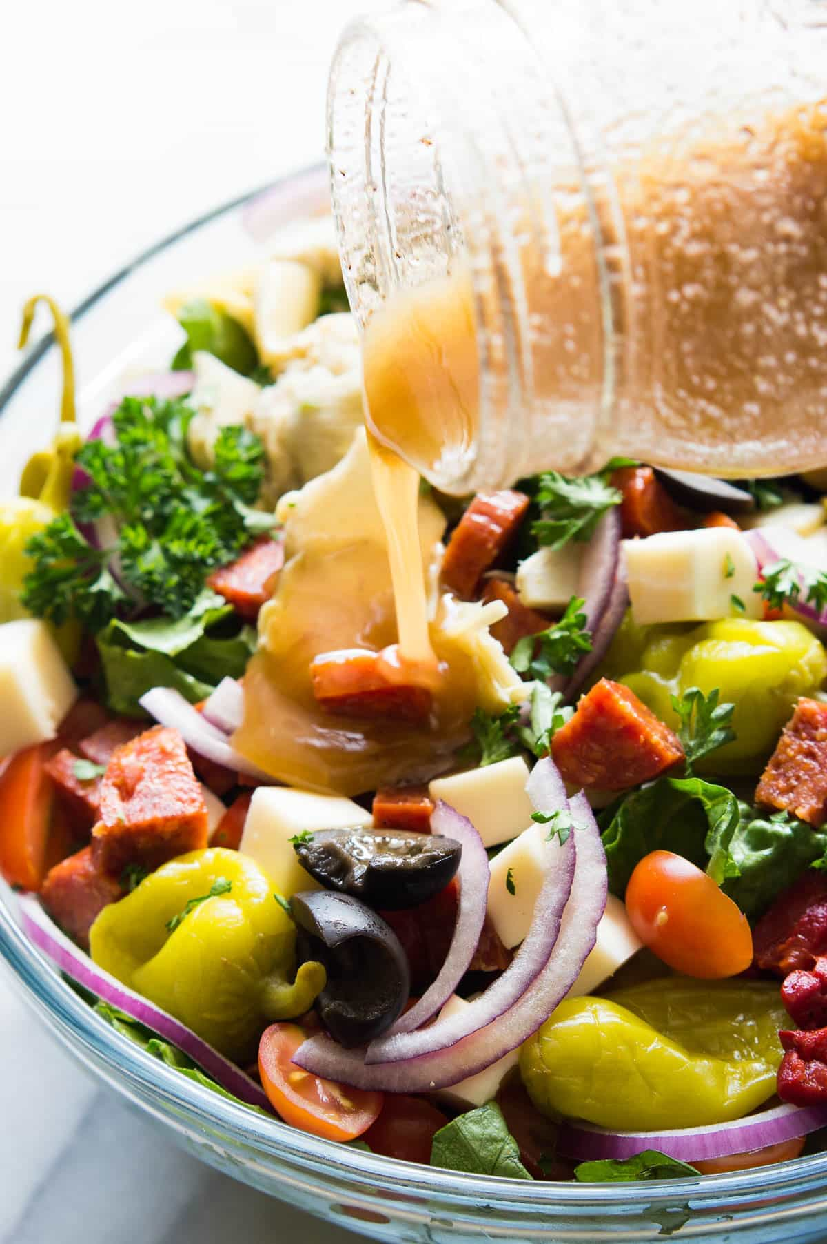 Antipasto Salad! The perfect side dish to go along with your Italian meals, loaded with artichoke hearts, roasted red peppers, olives, pepperoni, and fresh mozzarella! Not to mention drizzled with an easy to make vinaigrette made with pantry items!
