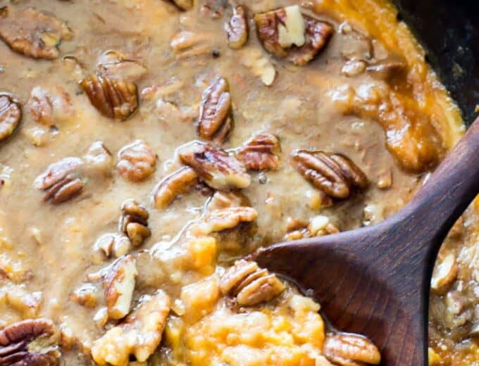 A slow cooker filled with sweet potato casserole topped with brown sugar pecan topping.