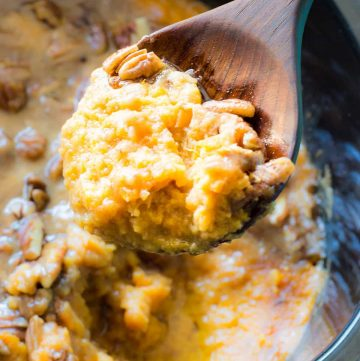 Wooden Spoon scooping up sweet potato casserole with a sweet brown sugar pecan topping.