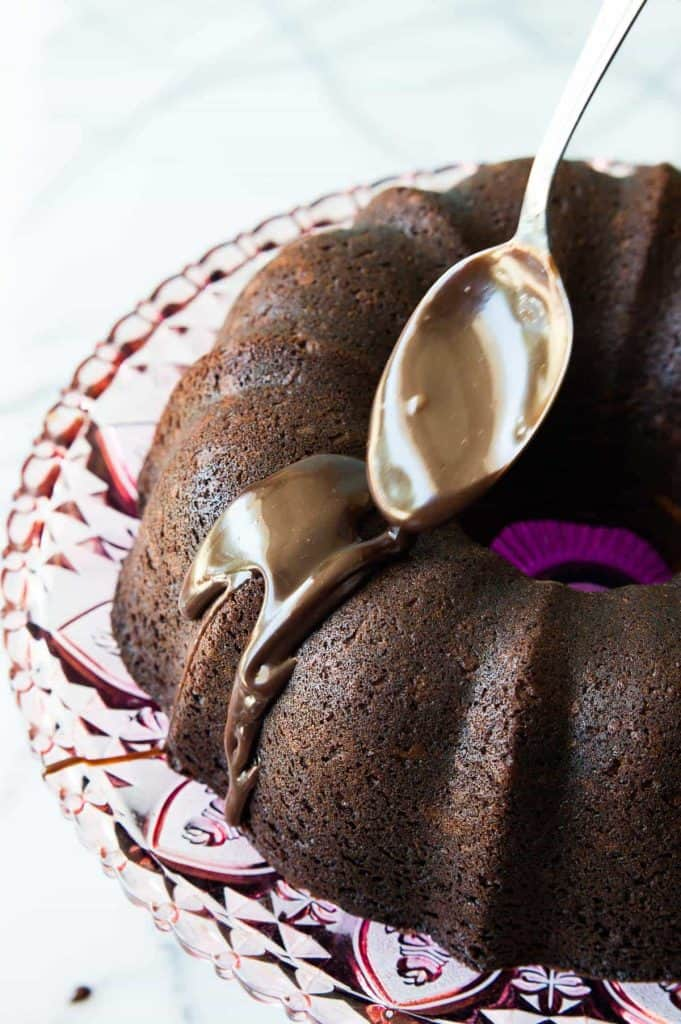 Chocolate Bundt Cake with Pumpkin Cheesecake Swirl! This ultra moist and fudgy chocolate bundt cake has a surprise, luscious pumpkin spice cheesecake swirl right in the middle of it! Plus it's all topped with a decadent chocolate ganache drizzle. So easy to make this cake is sure to impress!