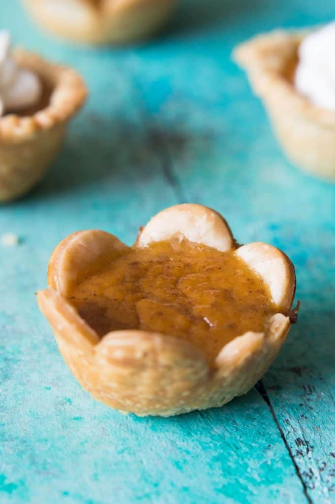 Mini Pumpkin Pies. Buttery, flakey pie crust filled with creamy pumpkin pie, spiced with cinnamon, nutmeg and cloves. Topped with homemade whipped cream. All in a bite size portion! Perfect for family get togethers and gatherings. These little treats will disappear FAST and everyone will be wanting more!