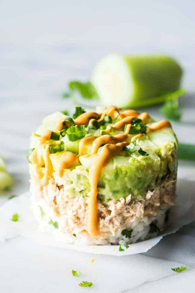 Salmon Stacks!! This super simple recipe is the perfect light and fresh snack, lunch, or light dinner! Sure to impress!!! This dish has layers of fluffy cilantro, lime rice. Salmon mixed with a spicy mayo. Smooth and creamy avocado. And fresh and cool cucumber. Forget getting that pricey sushi! Make this scrumptious snack at home!
