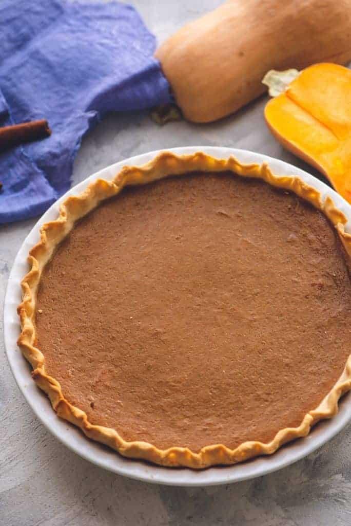 Whole butternut squash pie in a pie dish.