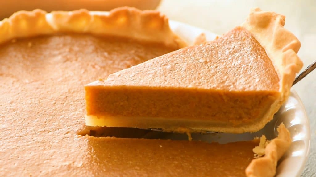 Slice of butternut squash pie being removed from a whole pie.