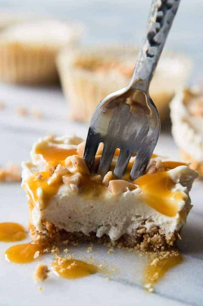 Almost NO BAKE Salted Caramel Toffee Cheesecakes! Smooth and creamy no bake salted caramel cheesecake with bits of toffee on top of a toffee graham cracker crust. All topped with little bits of toffee and a delightful salted caramel drizzle.