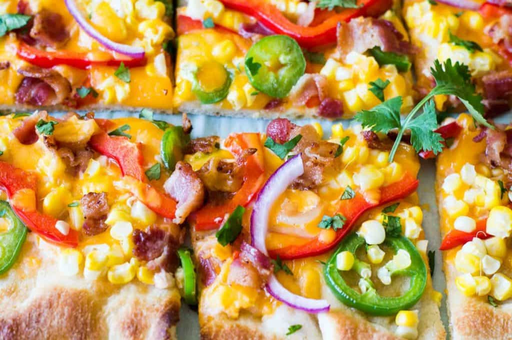 Tex Mex Pizza! This QUICK and EASY pizza is bursting with fresh flavor! Loaded up with bacon, corn, jalapeños and plenty of chipotle dressing. This is a family friendly dinner that will have everyone going back for seconds. Trust me!