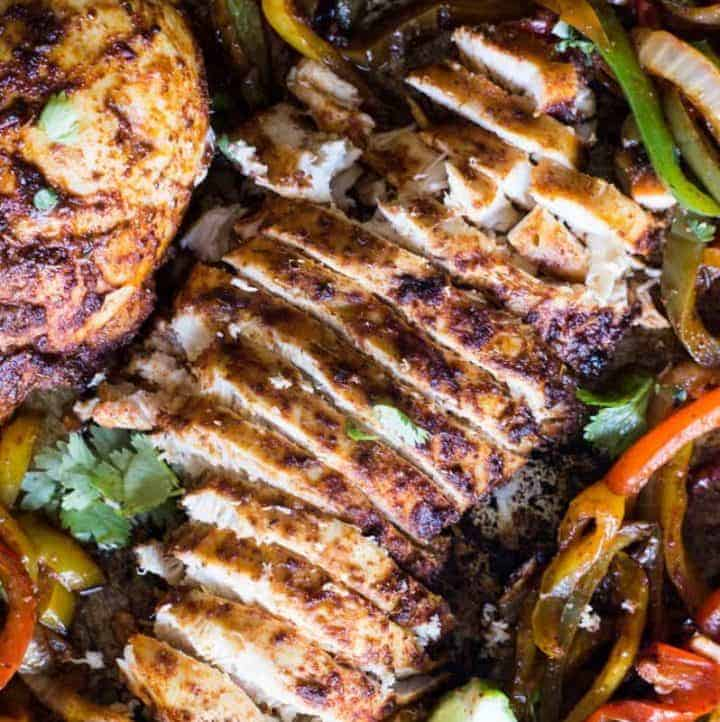 Sheet Pan Chicken Fajitas. An easy to put together dinner that is full of flavor and only uses ONE PAN! Juicy chicken seasoned with a homemade fajita seasoning is mixed with brightly colored bell peppers and onion for a classic tex mex meal. The entire family will love this one!
