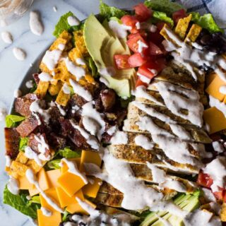 Southwest Grilled Chicken Salad with Candied Bacon. This salad is loaded with grilled chicken, fresh juicy tomato, creamy avocado, crunchy tortilla strips, black beans, cheddar cheese, and sweet and salty candied bacon. All drizzled with a homemade salsa ranch that is truly addicting!