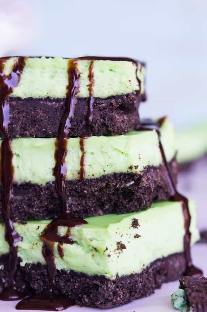 Mint Cheesecake Bars! A cool and creamy mint cheesecake baked on top of a mint oreo crust. Drizzle with some extra chocolate for a decadent treat! The fun green color makes this dessert perfect for St. Patrick's Day!