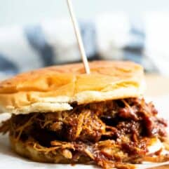 Slow cooker pulled pork mixed with a Texas style BBQ sauce on a bun making a pulled pork sandwich.