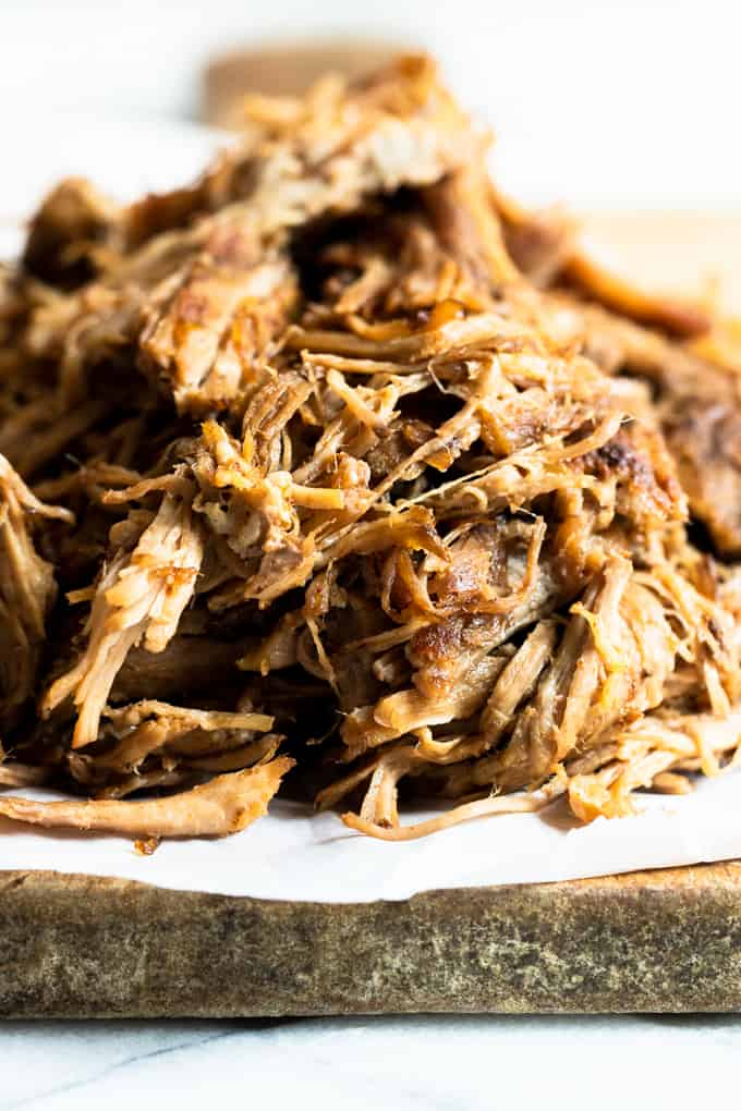 Pulled Pork that has been made in a slow cooker on a cutting board, shredded.