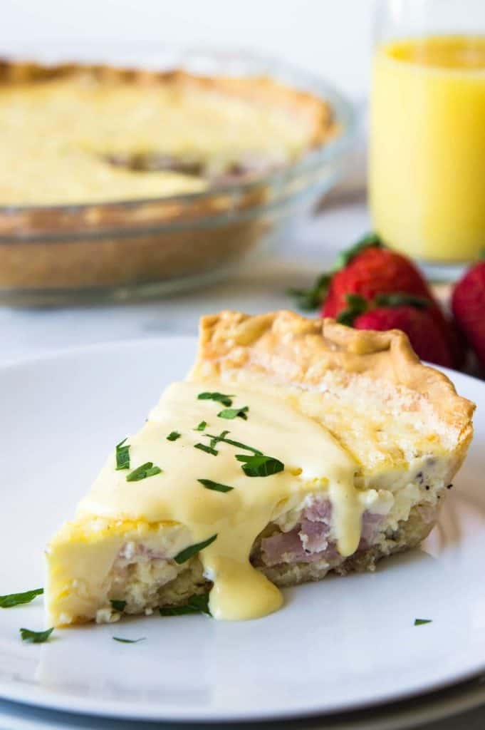 Eggs Benedict quiche served on a white plate, topped with hollandaise sauce and sprinkled with fresh parsley.