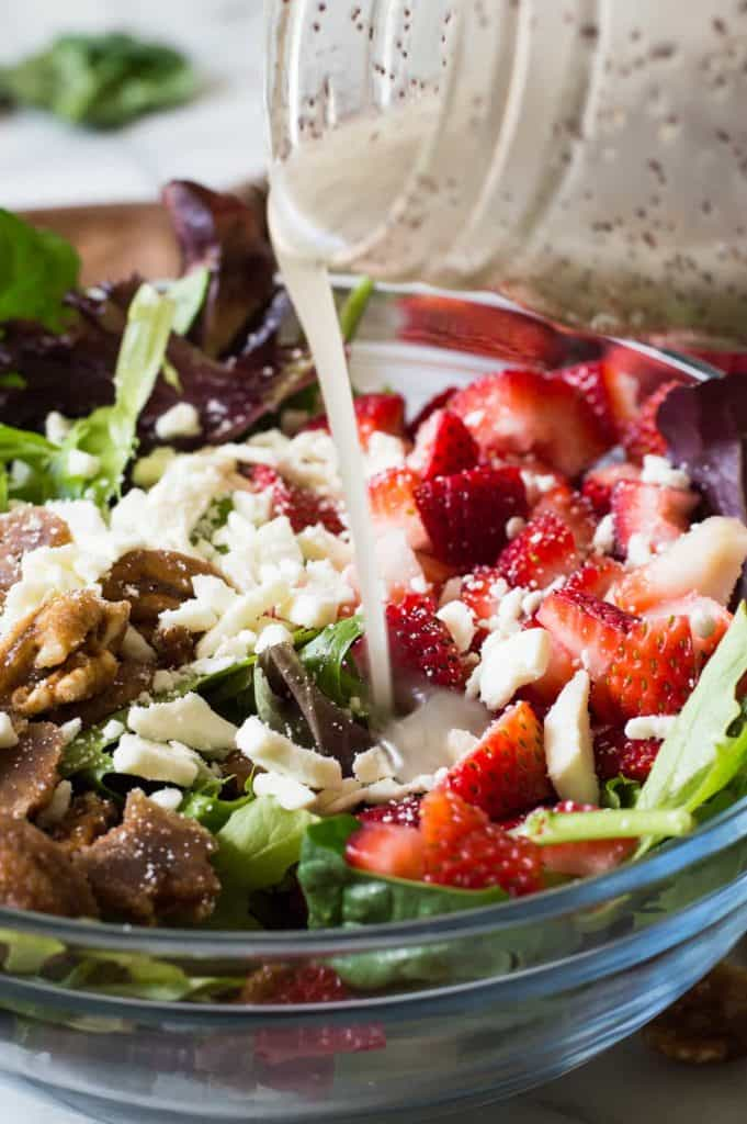 Strawberry Salad with Poppyseed Dressing. This salad is loaded up with fresh strawberries, candied pecans, feta cheese and drizzled with an easy to make sweet poppyseed dressing. Perfect dish for springtime!