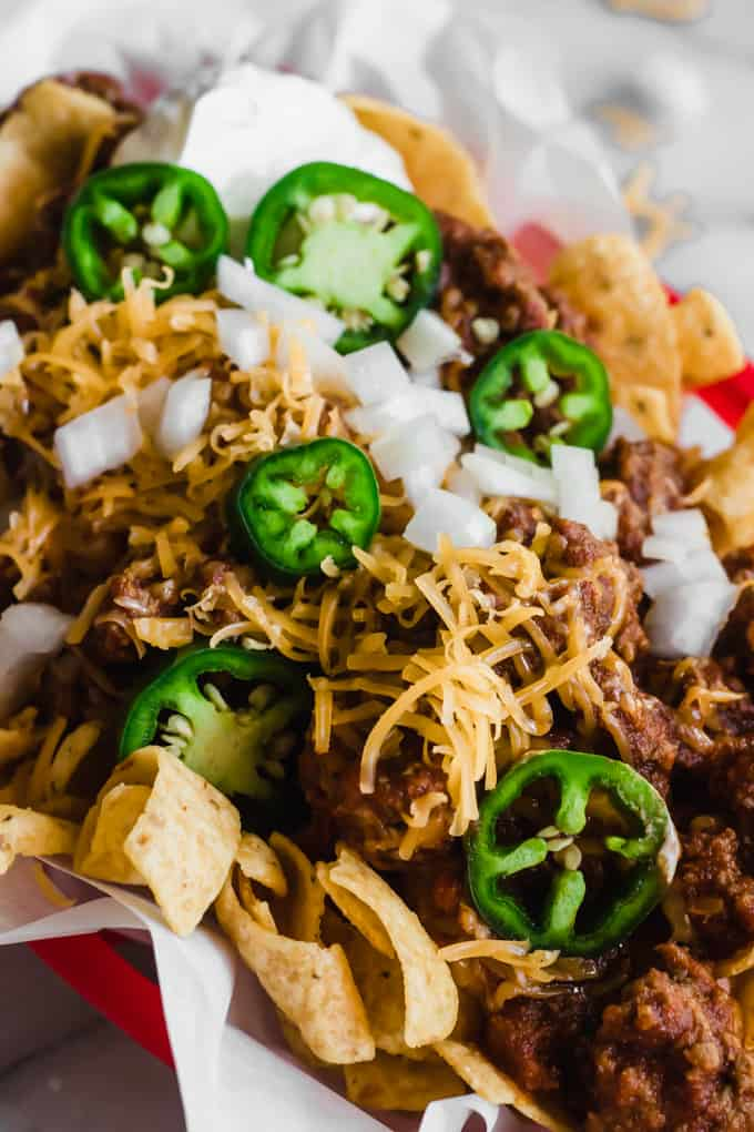 Frito pie made with Texas chili recipe topped with cheese, onion, sour cream and jalapeno.