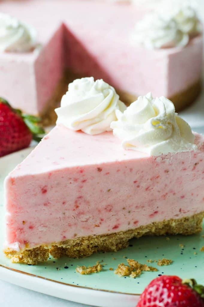 No Bake Frozen Strawberry Yogurt Pie! This frozen pie is perfect for warmer weather! No baking needed, and the pie itself is a creamy cool strawberry and cream flavor. Made with greek yogurt, real cream, and fresh strawberry puree! All on top of a pretzel crust.