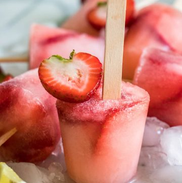 Strawberry Lemonade Popsicles!  Homemade lemonade and fresh cut strawberries meld together to create refreshing popsicles loaded with a sweet lemon flavor.