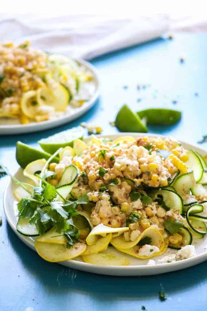 Mexican Street Corn Zucchini Pasta!  Fresh corn loaded up with lime juice, queso, and chili powder on top of summer zucchini and squash.  The perfect light and easy dish for hot summer days!