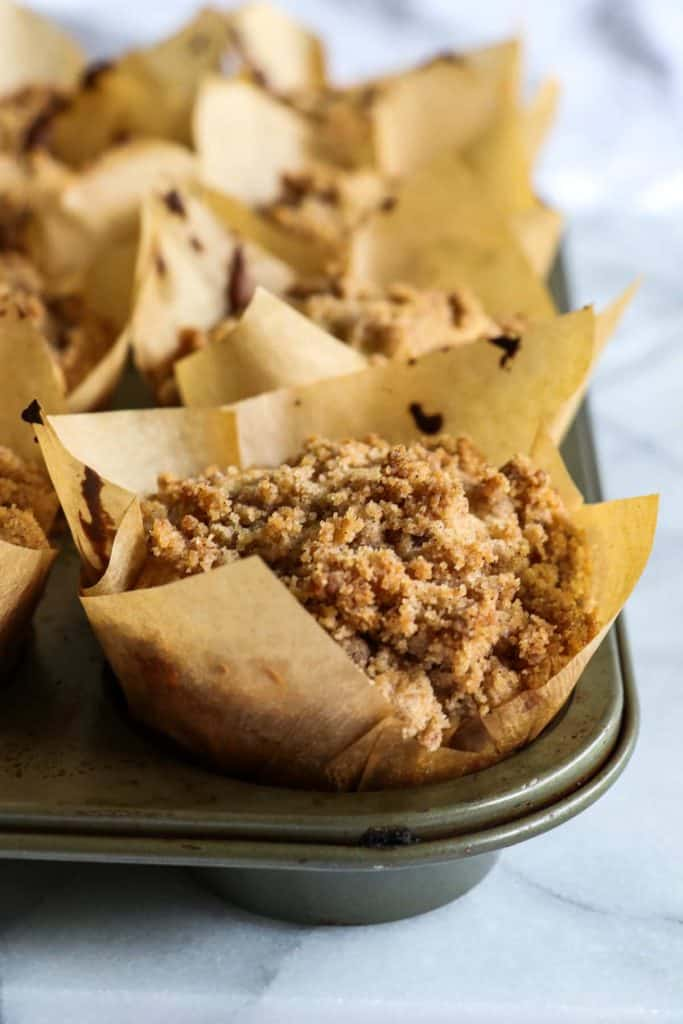 Muffin tin filled with apple crumb muffins in bakery brown papers.
