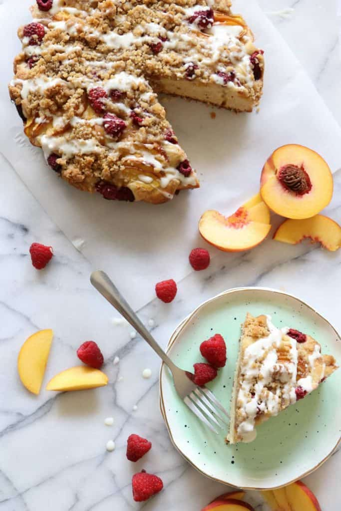 Peach Raspberry Crumb Cake!  A moist cake topped with fresh juicy peaches and sweet raspberries.  All covered in a sweet brown sugar crumb.