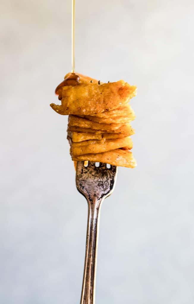 Fork being held up with a bite of stacked sweet potato pancakes and syrup being drizzled over it.