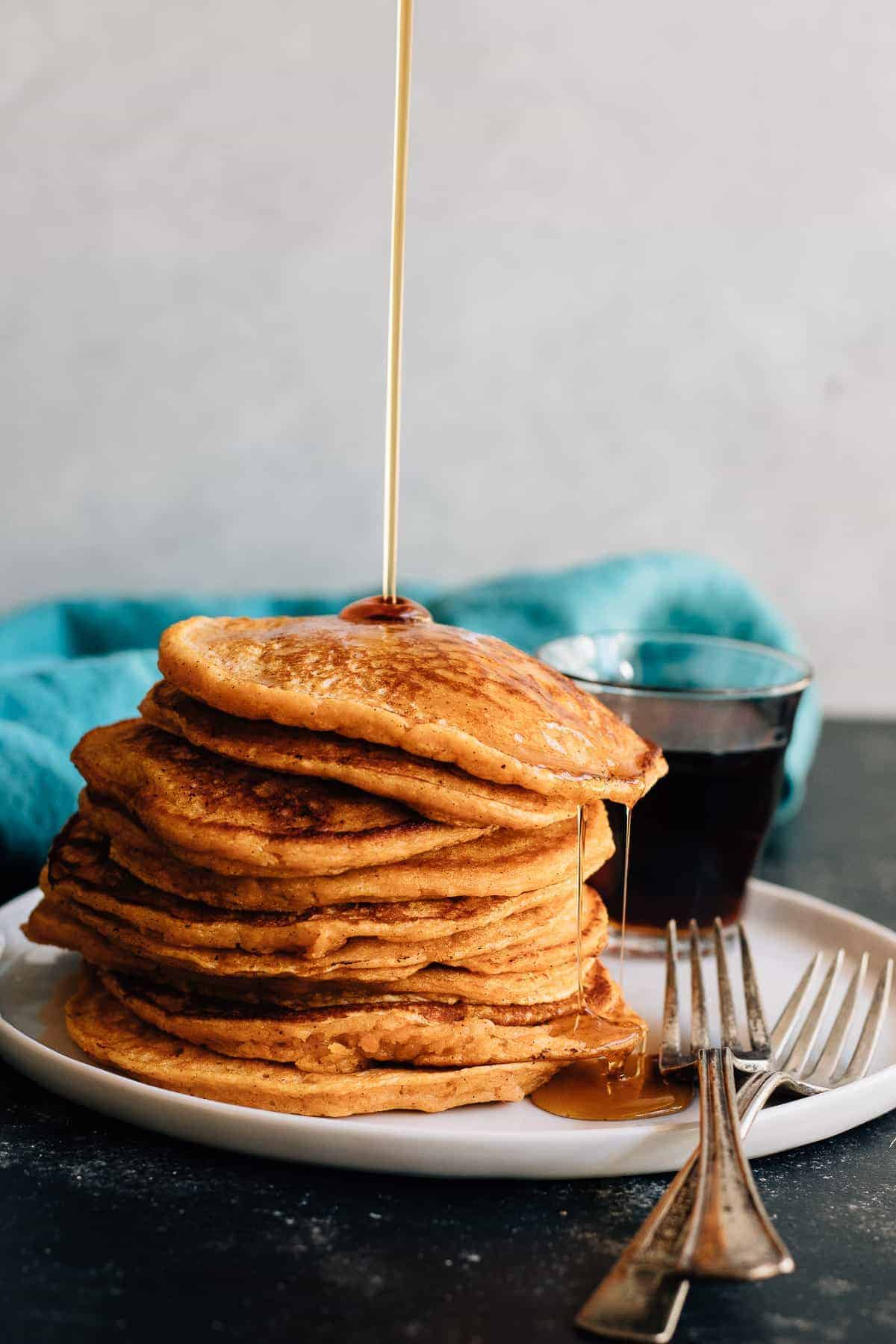 Soft and fluffy sweet potato pancakes made to the extreme with an overdose of spices and sweetened with maple syrup. Fall breakfast perfection.