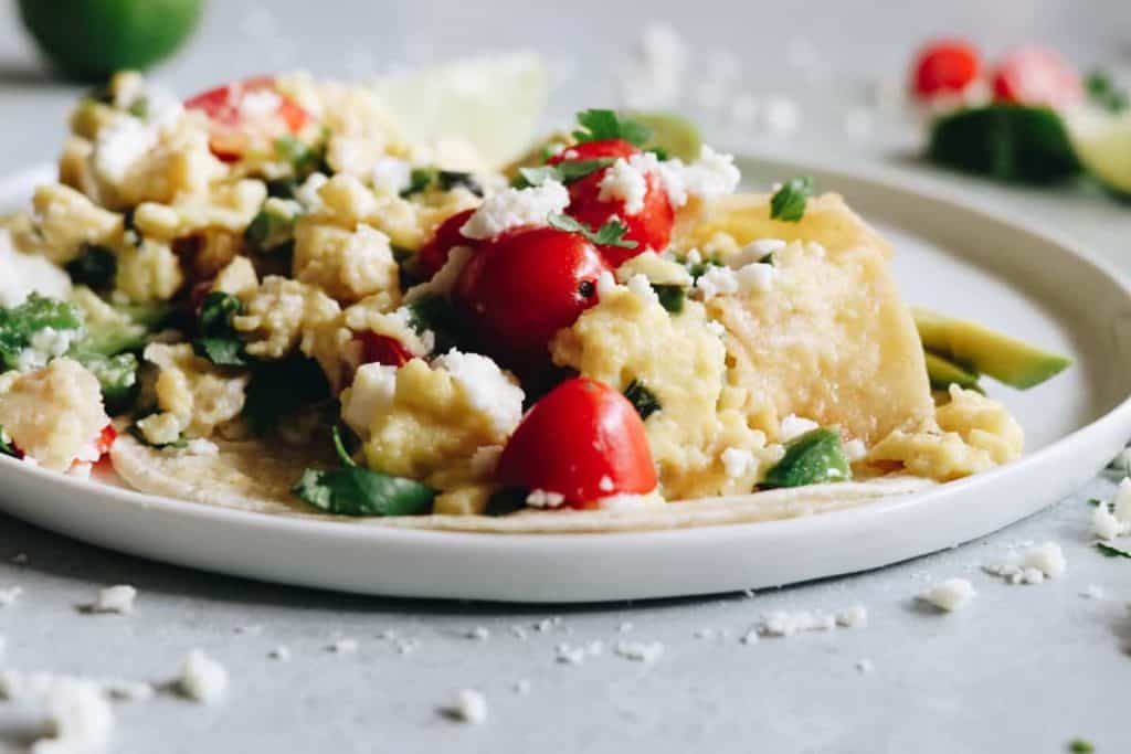 Easy migas are the Tex-Mex way to start your day! Soft and cheesy scrambled eggs loaded up with peppers, onion, and fried tortillas.