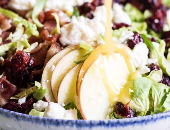 Finely chopped brussels sprouts make the best salad! Loaded up with bacon, feta, cranberries, and apples. All drizzled with a homemade bacon vinaigrette.