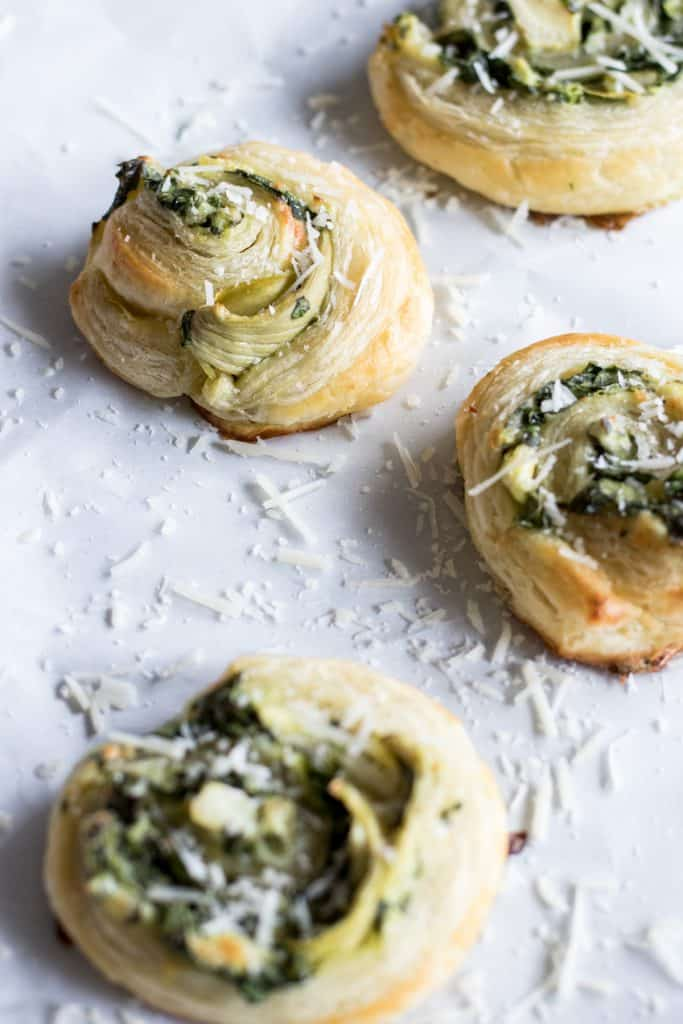 Puff Pastry Spinach and Artichoke Pinwheels. This easy to put together appetizer is perfect for any party or just as a snack. Loaded with fresh spinach, artichoke, and lots of cheese!