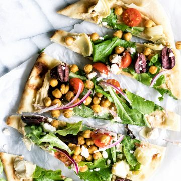 Close up of sliced flatbread pizza layered with hummus and toppings.