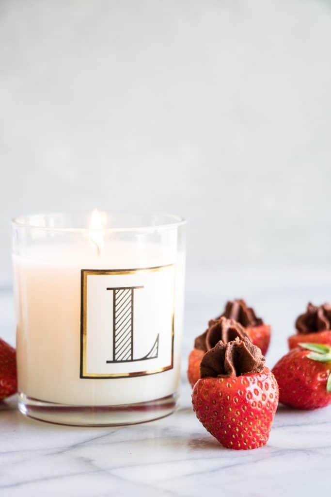 debi lilly designs alphabet candle lit with chocolate mousse filled strawberries next to it.