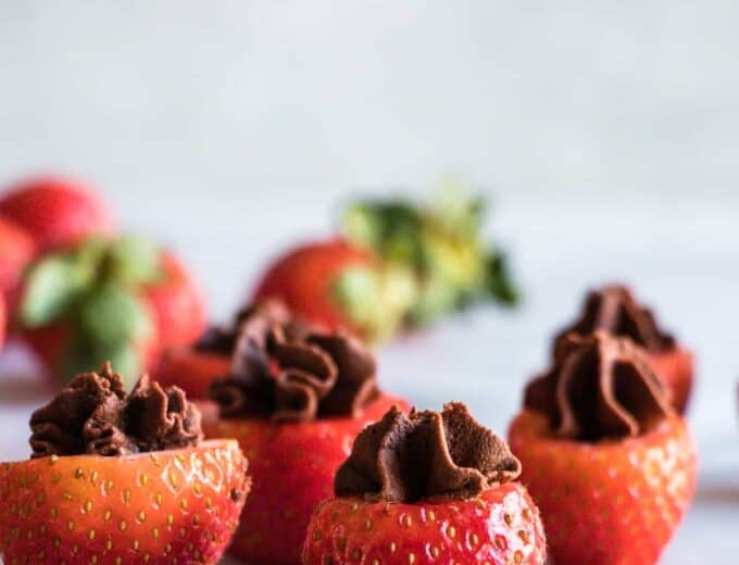 Chocolate Mousse filled strawberries and uncut strawberries in the background.