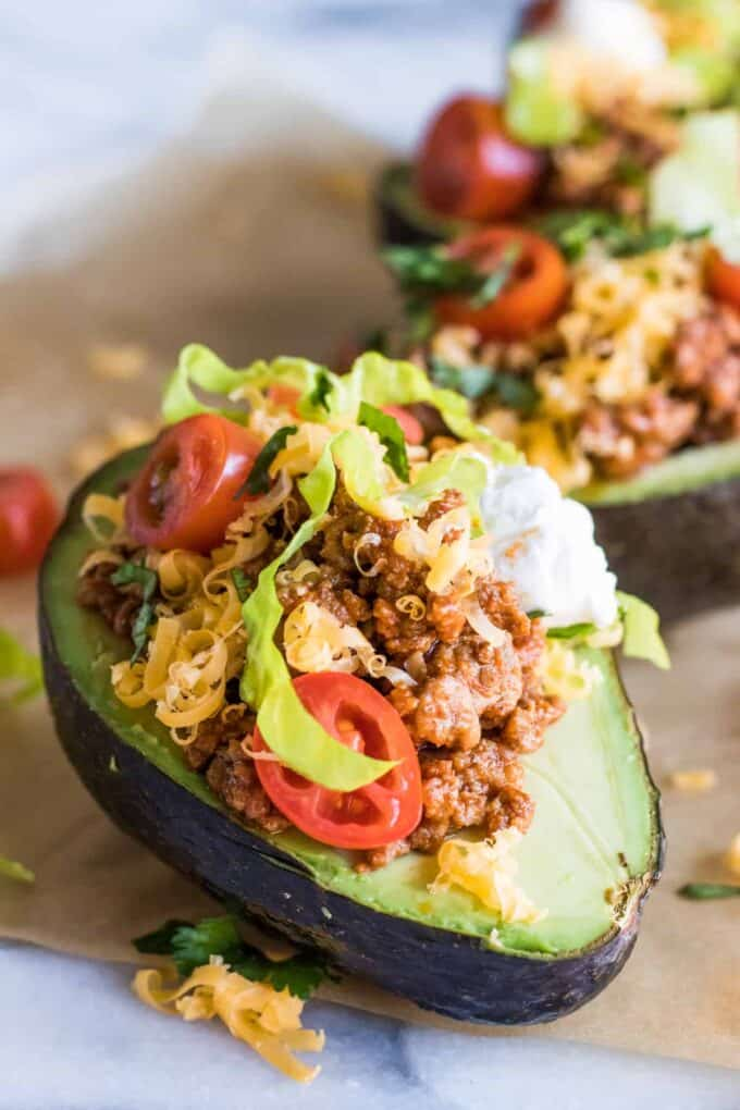 Close up of halved avocado stuffed with taco meat, cheese, lettuce, tomato and sour cream.