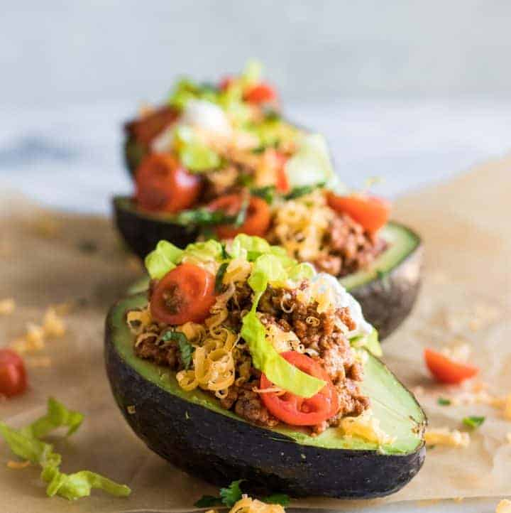 Row of taco stuffed avocado halves.