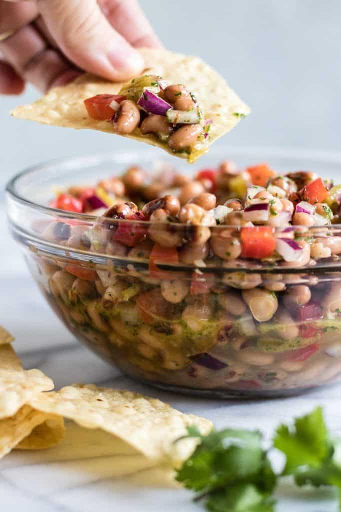 A chip dipping into a bowl full of Texas caviar.