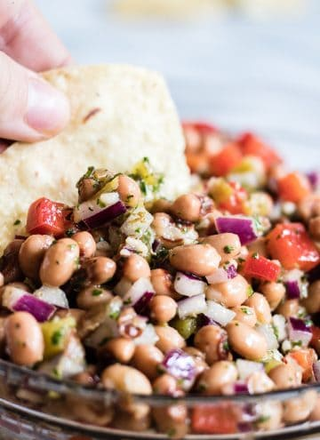 A close up of a tortilla chip dipping into Texas caviar. Black eyed peas, red onion, red bell pepper and green chiles all covered in a vinaigrette.