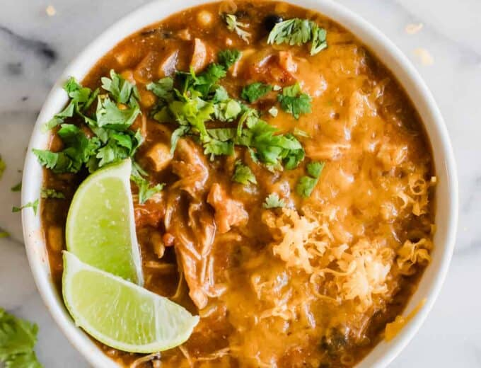 A bowl filled with chicken enchilada soup topped with cheese, cilantro and lime.