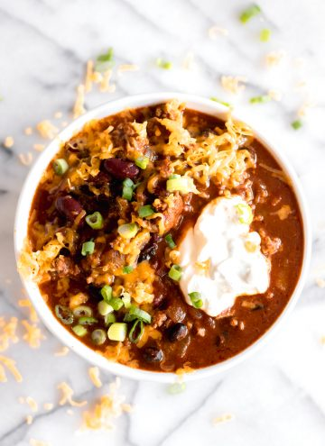 Overhead shot of bowl full of easy chili made with ground beef and beans topped with cheese, sour cream and green onions.