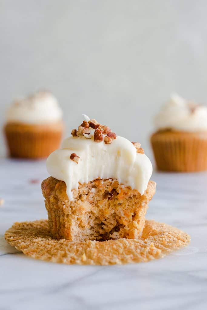 Moist and dense carrot cake cupcakes outside of the cupcake wrapper with a bite missing.