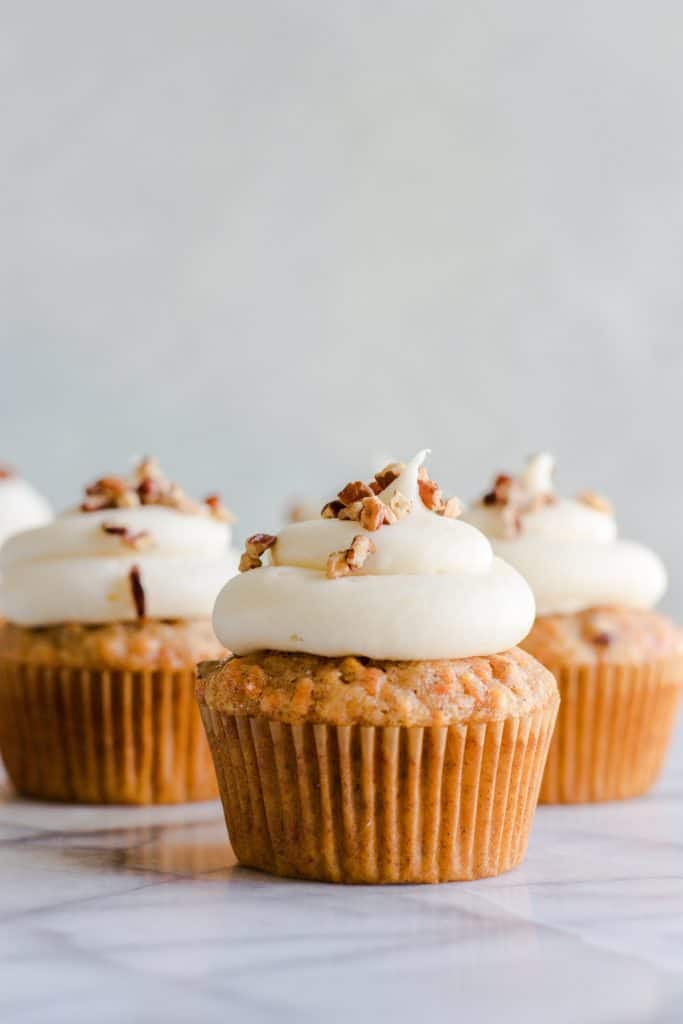 Carrot Cake cupcakes topped with a perfect swirl of fluffy cream cheese frosting. Topped with a sprinkle of chopped pecans.
