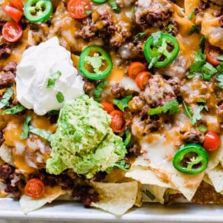 Sheet pan nachos layered with ground beef, cheese, tomatoes, cilantro, jalapeños, sour cream and guacamole.
